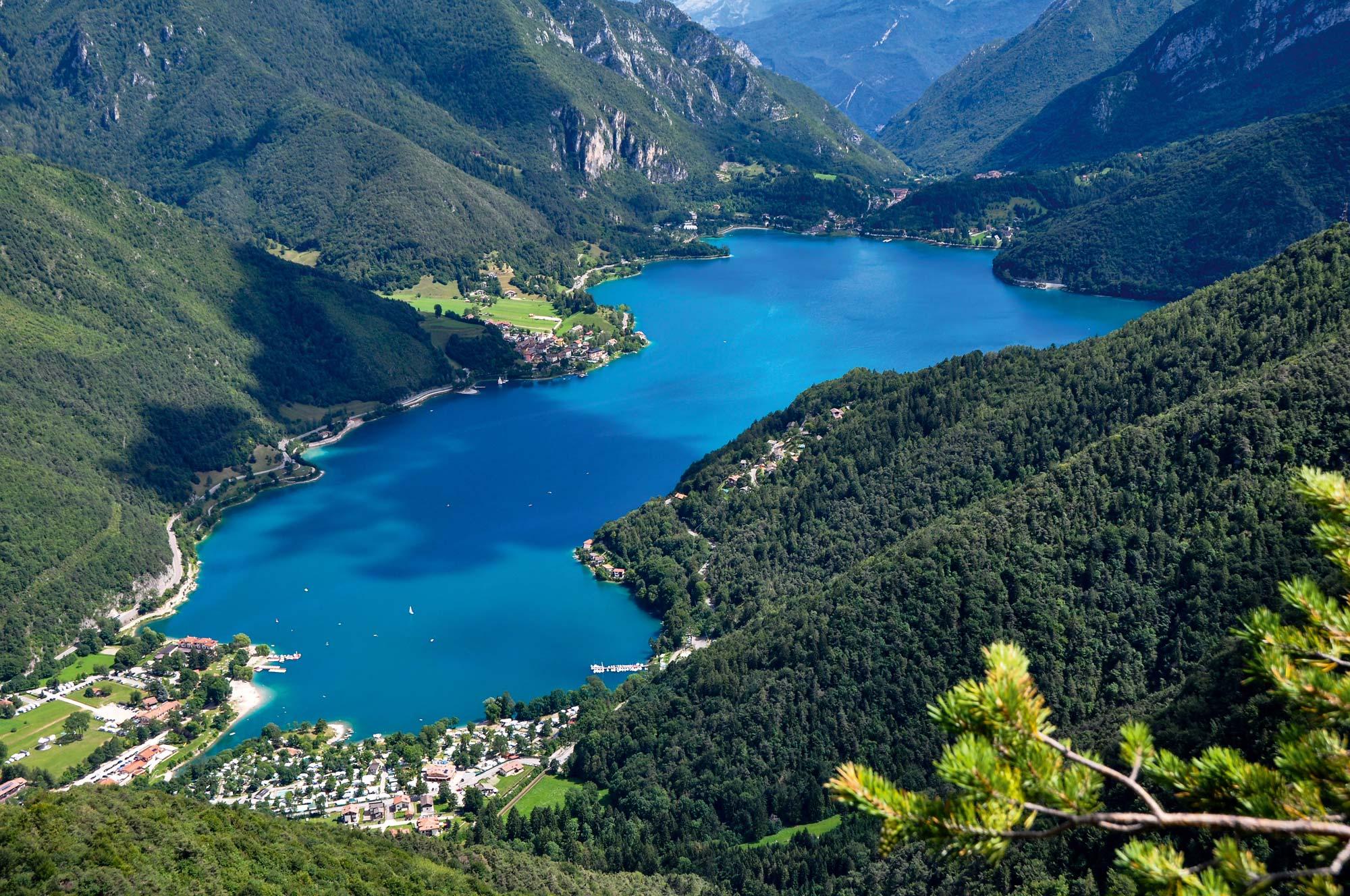 Grüne Wälder und Berge spiegeln sich im türkisblauen Wasser vom Ledrosee © Bruno Ferrari