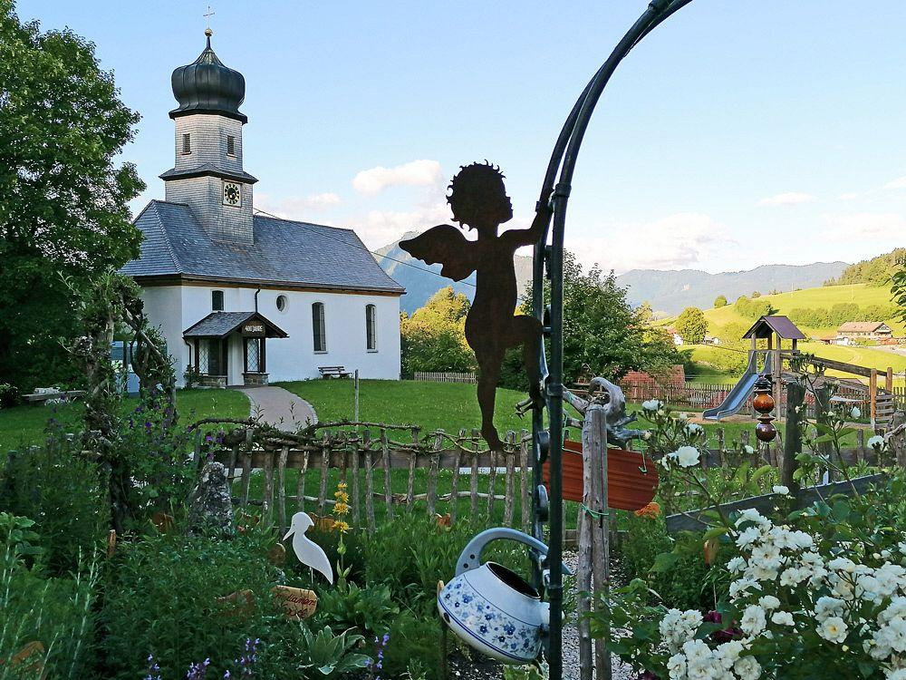 Der Kräutergarten gegenüber der Sennerei Gunzesried und die Kapelle St. Nikolaus im Hintergrund © Tourist-Info Blaichach